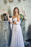 girl in a white evening dress standing by the fireplace Royalty Free Stock Photography