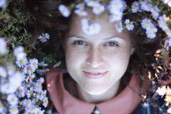 Girl among white flowers. Brunette girl sitting on a meadow among white flowers stock photo