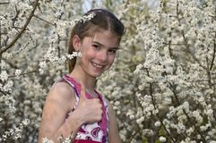 Girl with white flowers showing OK laughing Stock Photography