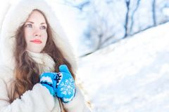 Girl in a white fur coat with blue eyes against a background of Stock Photography