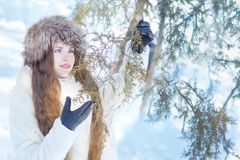 Girl in a white fur coat and a fur hat, with blue eyes and long royalty free stock images