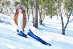 Girl in a white fur coat and a fur hat, with blue eyes and long stock photos