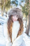 Girl in a white fur coat and a fur hat, with blue eyes and long royalty free stock image