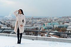 Girl in a white fur coat posing against the backdrop of the city. Beautiful girl in a white fur coat posing against the backdrop of the city Royalty Free Stock Photos