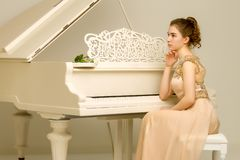 The girl is at the white grand piano. Beautiful little girl near a white grand piano. The concept of education and school, children`s creativity stock images