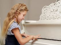 The girl is at the white grand piano. royalty free stock photography