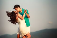 girl in white and guy kiss under wind at dawn Stock Photo