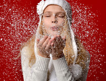 Girl in white hat blowing on the snow on her hands on red Royalty Free Stock Photography