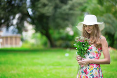Girl in white hat holding bunch of flowers Stock Images