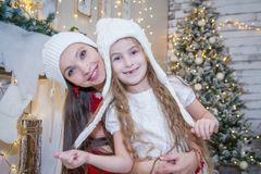 Girl in white hat with mother under Christmas tree Stock Photos