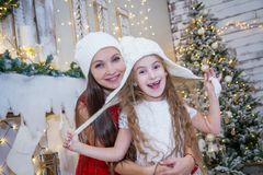 Girl in white hat with mother under Christmas tree Stock Photo