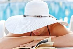 Girl in white hat reading a book in a lounge chair by the pool Royalty Free Stock Image