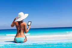 Girl with white hat reads kindle on beach Royalty Free Stock Photo