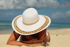 Girl with white hat on sand Stock Images