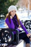 Girl in white hat sitting on a bench in winter Stock Photography