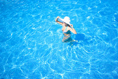 Girl, white hat and swimming pool Stock Photography