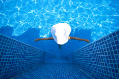 Girl, white hat and swimming pool Royalty Free Stock Image