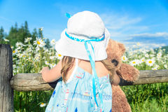 Girl in white hat with teddy bear looking at the beautiful field Royalty Free Stock Images