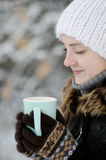 Girl in a white hat in winter with cup of tea, side view, closeup Stock Image