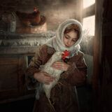 A girl in a white headscarf is holding a white chicken