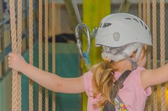 The girl in the white helmet in the adventure Park, closeup. Close up, the adventure Park the kid in the white helmet Royalty Free Stock Photos