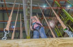 Girl in a white helmet at the adventure Park at the height of ho. The rope at the height of holds in the adventure Park the kid in the white helmet Stock Images