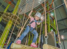 The girl in the white helmet in the adventure Park holds on to t. Holding the ropes in adventure Park the kid in the white helmet Royalty Free Stock Images