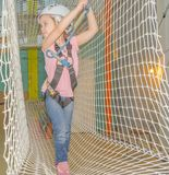 The girl in the white helmet in the adventure Park, overcomes ob Royalty Free Stock Photo