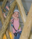 The girl in the white helmet in the adventure Park, overcomes ob. To clear obstacles in the adventure Park the kid in the white helmet Stock Photo