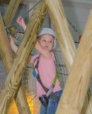 The girl in the white helmet in the adventure Park, overcomes ob Stock Photo