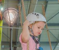 Girl in a white helmet and insurance in adventure Park. In the adventure Park the kid in the white helmet and insurance Royalty Free Stock Photo