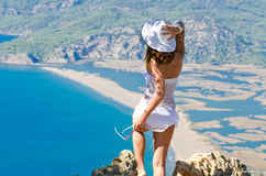 Girl in white on a high cliff Stock Images