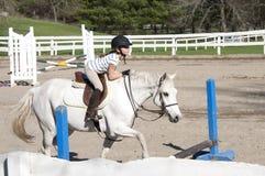 Girl at horseback riding lesson. Royalty Free Stock Images