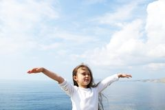 Girl in  white jacket. Girl in a white jacket standing arms outstretched to the side against the sea Royalty Free Stock Photography