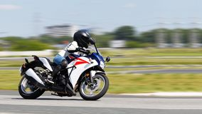 The girl in a white jacket and blue jeans race on a motorcycle. Motion blur. Copyspace royalty free stock photo
