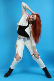 Girl in a white jacket and in ragged jeans Royalty Free Stock Image