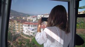 A woman takes pictures of a mountain of Alanya from the funicular on the phone. A girl in a white jacket takes pictures of the mountain of Alanya stock video