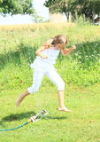 Girl in white jumping thru sprinkler Stock Photography