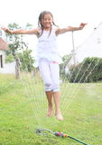 Girl in white jumping thru sprinkler Stock Photos