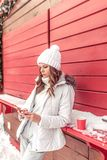 A girl in white jumpsuit and jacket in winter hat. Standing at red wooden counter in his hand holding phone. A woman stock photo