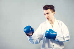 Girl in a white kimono and blue gloves is worth in combat drain, ready to attack, Royalty Free Stock Photo
