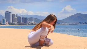 Girl in white lace costume demonstrates yoga asana child's pose on beach stock video