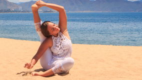 girl in white lace costume shows yoga asana leg behind head on beach stock video footage