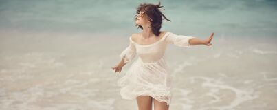 A girl in a white lace dress walks along the surf line by the sea
