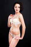 Girl in white lacy underwear on black background Royalty Free Stock Photos