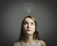 Girl in white and light bulb Stock Images