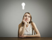 Girl in white and light bulb Stock Photos