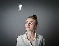 Girl in white and light bulb Royalty Free Stock Photo