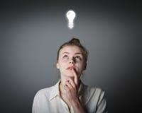 Girl in white and light bulb Stock Image