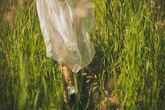 A girl in a white light chiffon dress fluttering in the wind, walking in the tall green grass in the field, on a Sunny summer day stock photos
